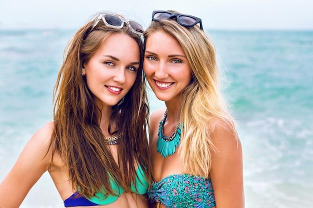 2つのかなり新鮮な若いブルネットとブロンドの親友の女の子のライフスタイルファッションポートレートを閉じます。熱帯の島のビーチで休暇を過ごし、ビキニサングラスと明るい宝石を着用しています。