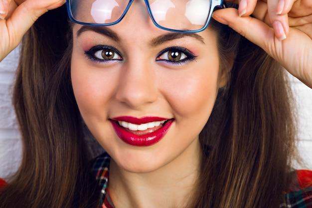 Закройте вверх по портрету моды образа жизни молодой женщины с ярким составом и двумя забавными хвостиками, удивленными положительными эмоциями.