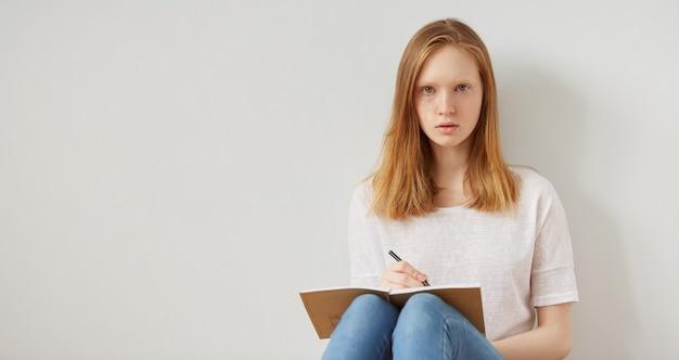 Chiuda sull'immagine di stile di vita della ragazza adolescente abbastanza giovane che si siede sul suo pavimento e che prende le note