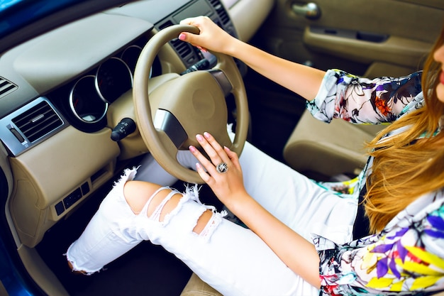 Close up lifestyle image of stylish woman driving her car, perfect manicure and accessory, vintage denim crazy pants, travel road concept.