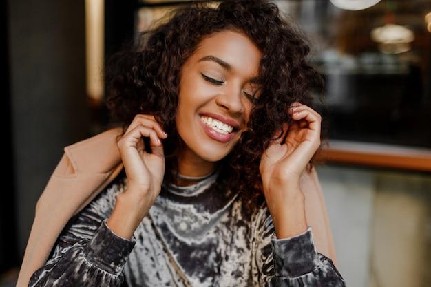 Close up lifestyle portrait of happy carefree black woman enjoying coffee break in paris.