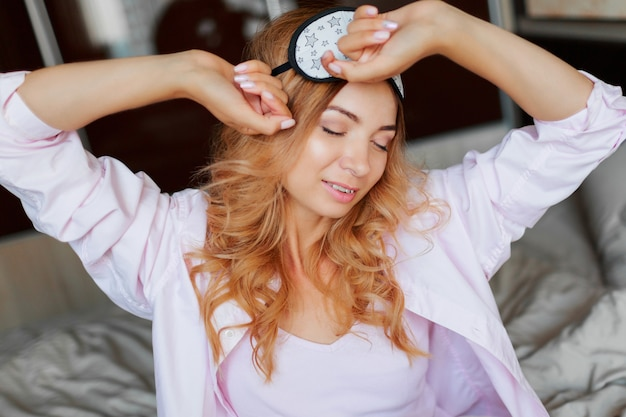 寝室のアイマスクでポーズをとって率直な笑顔で至福の女性のライフスタイルの肖像画を間近します。