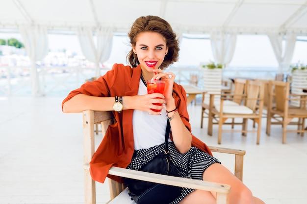 かわいいスタイリッシュな若い女性が屋外でポーズ、夏のカフェに座って、エキゾチックなカクテル、海の背景を飲むのライフスタイルの肖像画を間近します。明るい色。休暇気分。笑顔で楽しんでください。