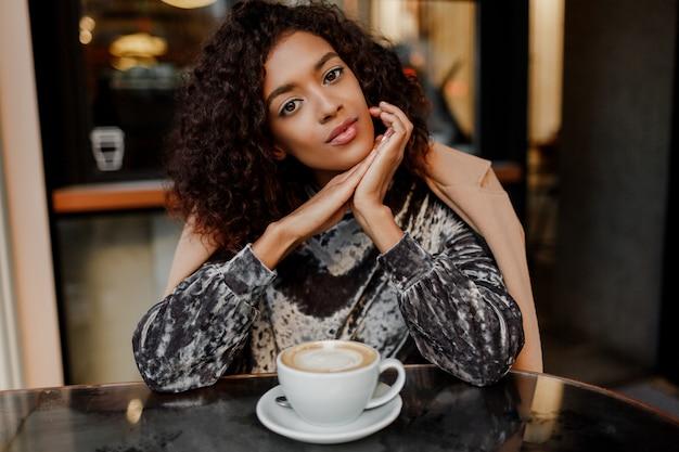 パリでコーヒーブレークを楽しんで幸せな屈託のない黒人女性のライフスタイルの肖像画を閉じます。