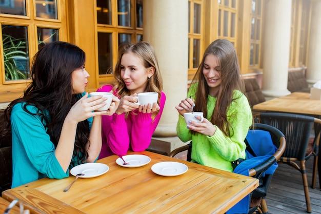 카페에 앉아서 뜨거운 티를 즐기는 세 명의 아름다운 젊은 여성의 라이프 스타일 초상화를 닫습니다. 밝은 네온 노란색, 분홍색 및 파란색 세련된 스웨터를 입고. 휴일, 음식 및 관광 개념.