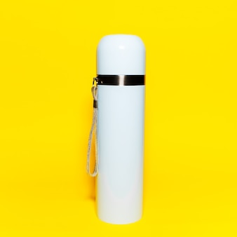 Close-up of light blue thermos isolated on yellow.