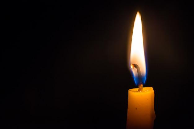 검정색 배경에서 밝게 타는 빛 촛불을 닫습니다.