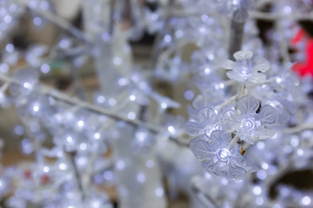 白いクリスマスのプラスチックの木の明るい花をクローズアップ装飾背景テクスチャの概念
