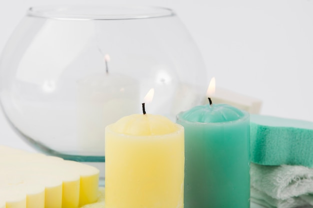Close-up of lighted yellow and green candle with sponges over white background