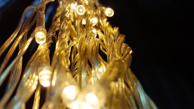 壁に花輪のライトを閉じます。黒の背景に輝く電気花輪。