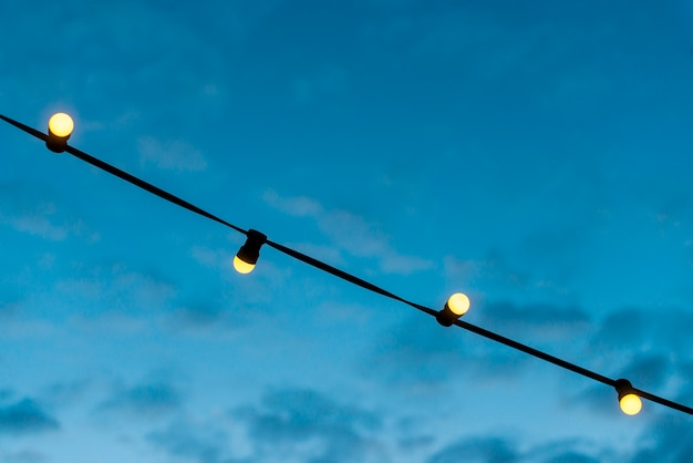 Close-up of a lights string with blue sky