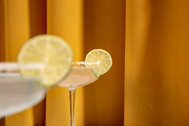 Close-up of lime slices over the edge of margarita cocktail glasses
