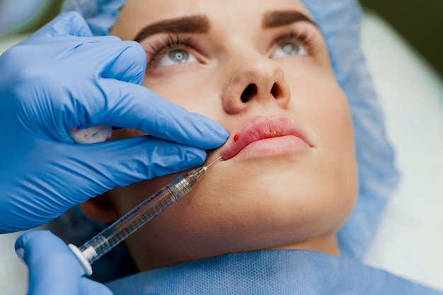 Close-up lips augmentation injections for attractive girl