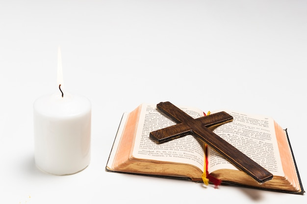 Close-up lit candle with holy book and cross