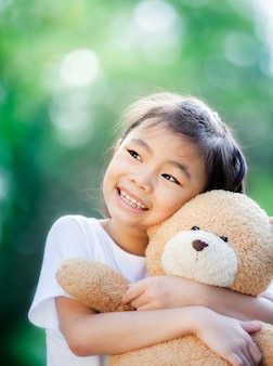 Close up on little asian girl hugging a teddy bear in park