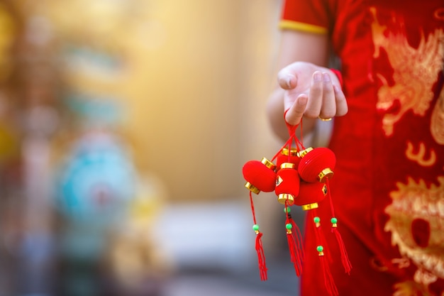 Close-up of little asian woman wearing red traditional chinese cheongsam, hold small lantern decorations for chinese new year