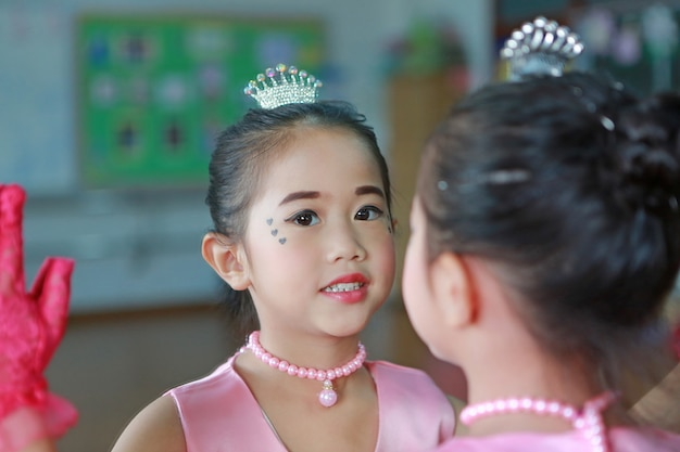 Close up little ballerina girl in a pink tutu posing with mirror reflection