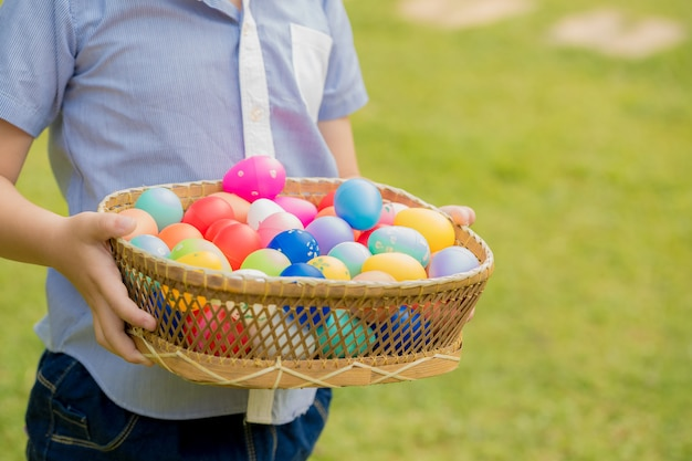 Close up little boy holding basket full of colorful easter eggs
