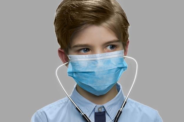 医療マスクを身に着けている小さな男の子を閉じます。灰色の背景に対してサージカルマスクと聴診器を身に着けている将来の医師がクローズアップ。