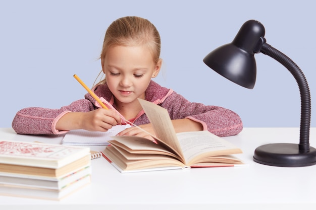 Close up little charming girl sits at white desk, does homework task, try to write composition or does sums, looks concentrated, uses reading lamp for good vision, isolated on blue wall.