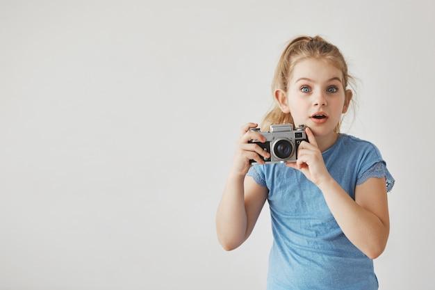 Primo piano di bambina carina con i capelli chiari in maglietta blu con espressione del viso sorpreso, tenendo la fotocamera in mano.