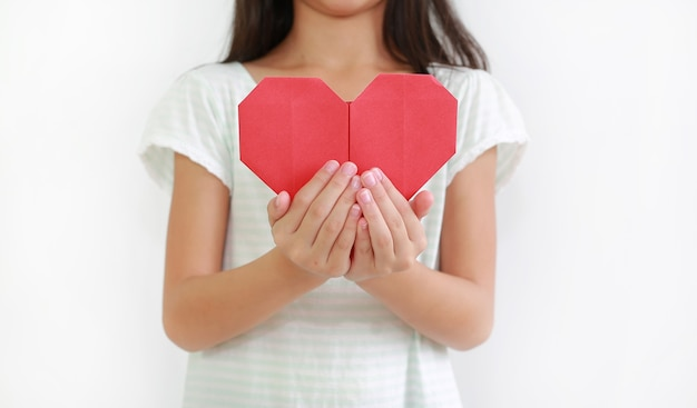 Close-up little girl child holding red heart sign against white background