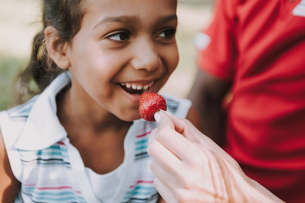 Close up. little girl eats strawberry on picnic.