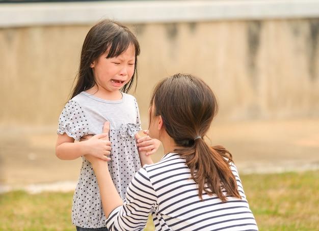 彼女の母親の腕の中で泣いている小さな女の子の顔を閉じます。