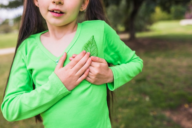 Close-up of a little girl holding fake green leaf near heart