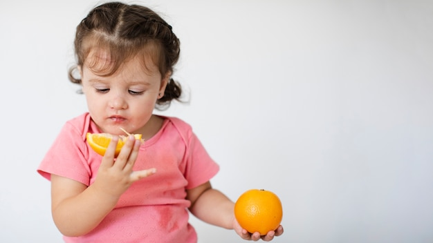 Close-up little girl looking at her oranges