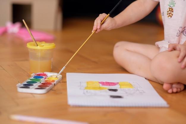 Крупным планом маленькая девочка, рисующая кистью