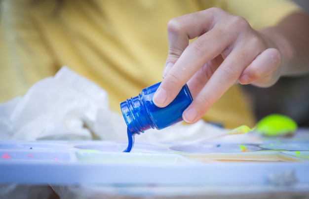 Close up of little girl's hand pouring blue ink to palette, creativity children concepts