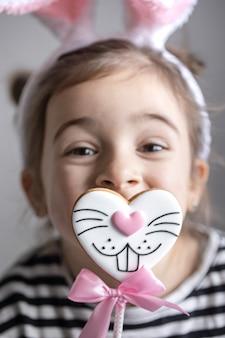 Primo piano di una bambina con pan di zenzero pasquale su un bastone a forma di faccia di coniglietto.