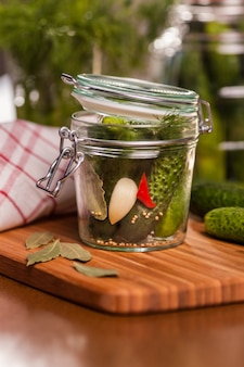 Close up of little jar with pickled cucumbers