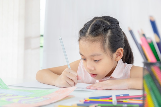Close up of little kid girl drawing with colorful pencils