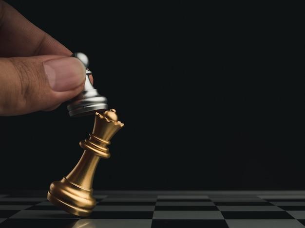 Крупным планом маленькая серебряная пешка ставит мат золотой королеве на шахматной доске на темном фоне с копией пространства. соревнования по шахматной игре. концепция стратегии, управления и лидерства.