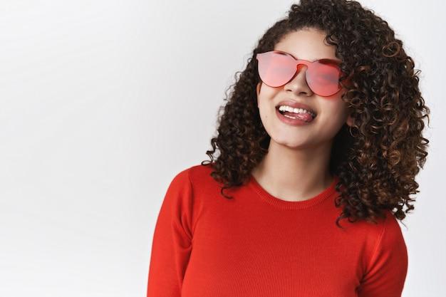 Close-up vivace elegante entusiasta moderna donna riccia acconciatura scura che indossa occhiali da sole rossi top sorridente ridendo felicemente mostra lingua divertente mimando godersi l'estate, in piedi muro bianco