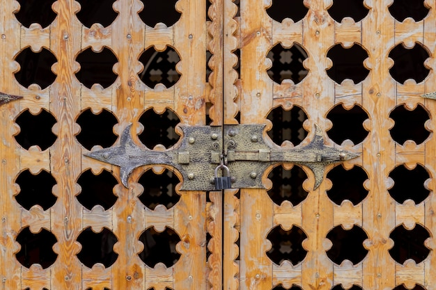 Close up locked carved wooden gate