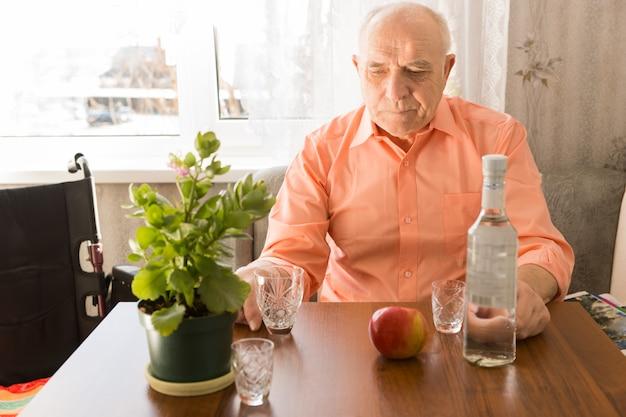 リンゴと緑の植物を上にして、テーブルで孤独に座っている高齢者の飲酒ワインをクローズアップします。