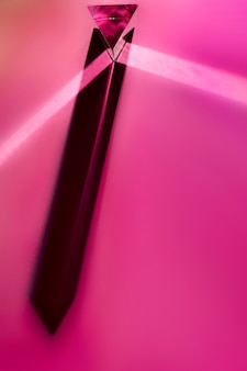 Close-up of long crystal prism with shadow on pink background