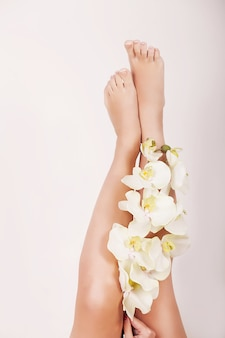 Close up of long female legs with perfect smooth soft skin and flowers