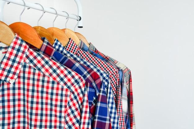 Close up of long sleeve red and blue checkered shirt on wooden hanger over white