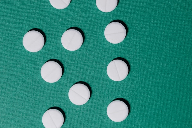 濃い緑色の背景にたくさんの錠剤をクローズアップ