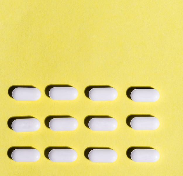 黄色の背景にたくさんの錠剤をクローズアップ