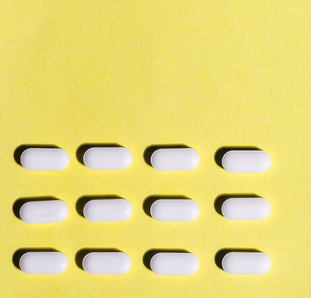 Close up lot of pills on a yellow background