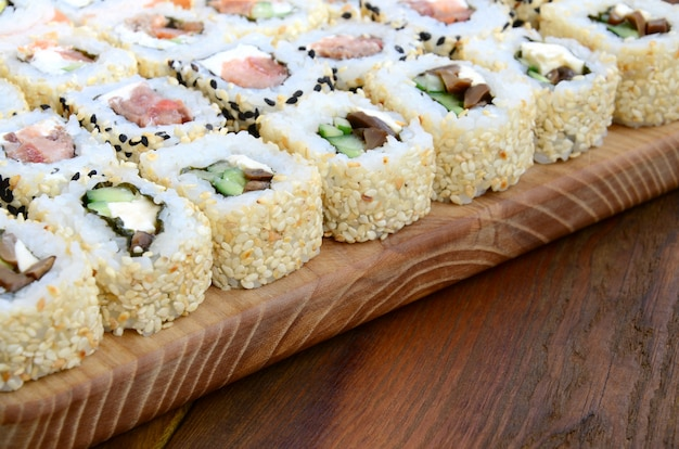 Close-up of a lot of sushi rolls with different fillings lie on a wooden surface.