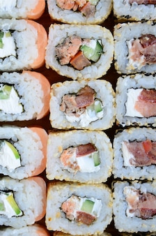 Close-up of a lot of sushi rolls with different fillings.