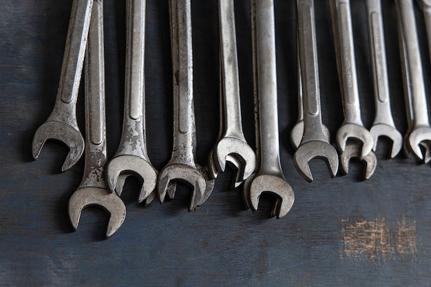 Close up a lot of wrench on old wooden board background.