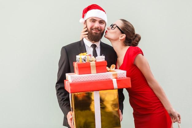 Крупным планом концепция любви красивая девушка поцеловать счастливого бизнесмена, потому что он подарил много подарков