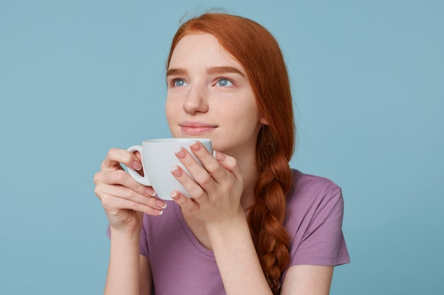 Close up of lovely beautiful red-haired girl smiling dreamingly looking upper left corner, keeps in hands big white cup with drink